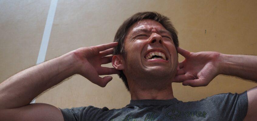 man plugging ears