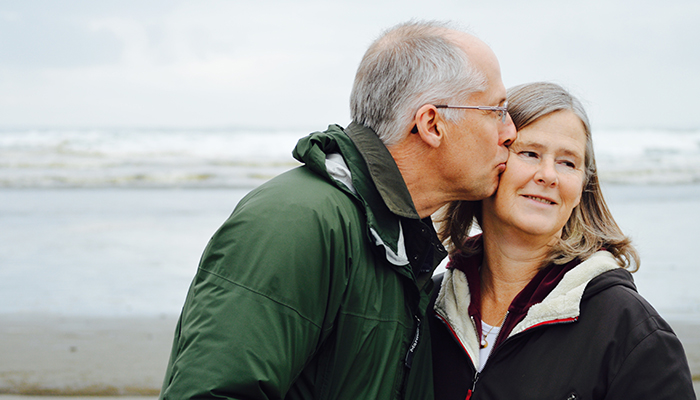 Older man in a hunter green jacket kissing a woman on the cheek with beach and waves behind them