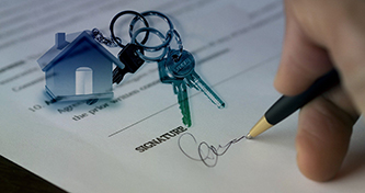close up of a person signing paperwork with a house keychain and keys next to it