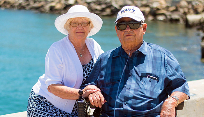 Elderly couple sitting by the water, woman in white blouse and hat, man in wheelchair and Navy baseball hat and sunglasses