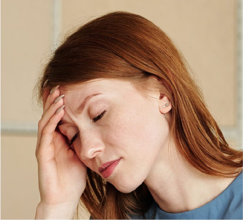 woman holding her forehead while experiencing a headache