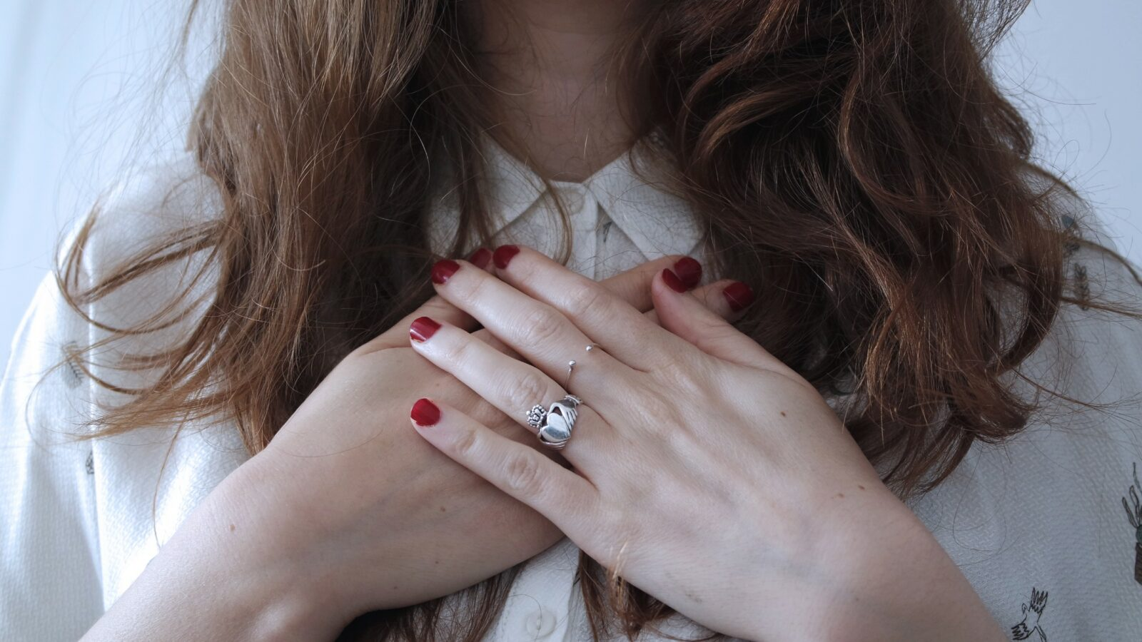 Close up of lady from chin down, primary focus on hands crossed under throat. Red nails and one ring.