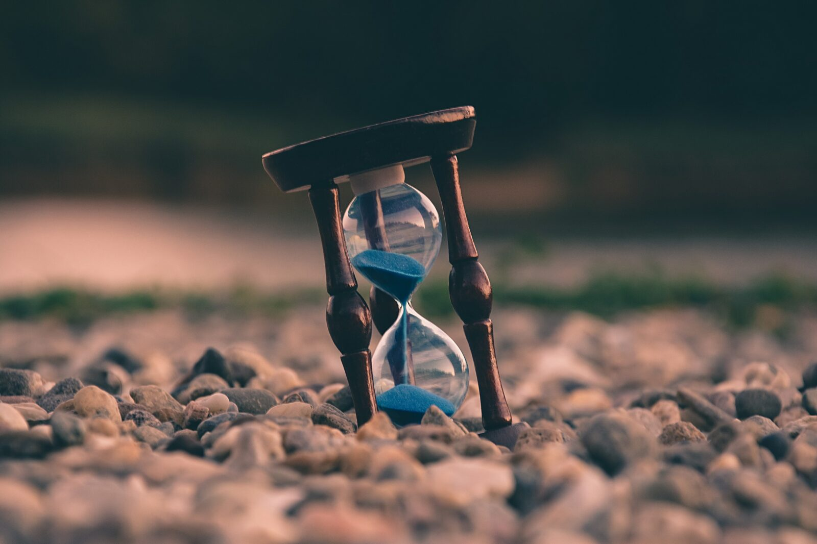 Hourglass with blue sand on pebble beach