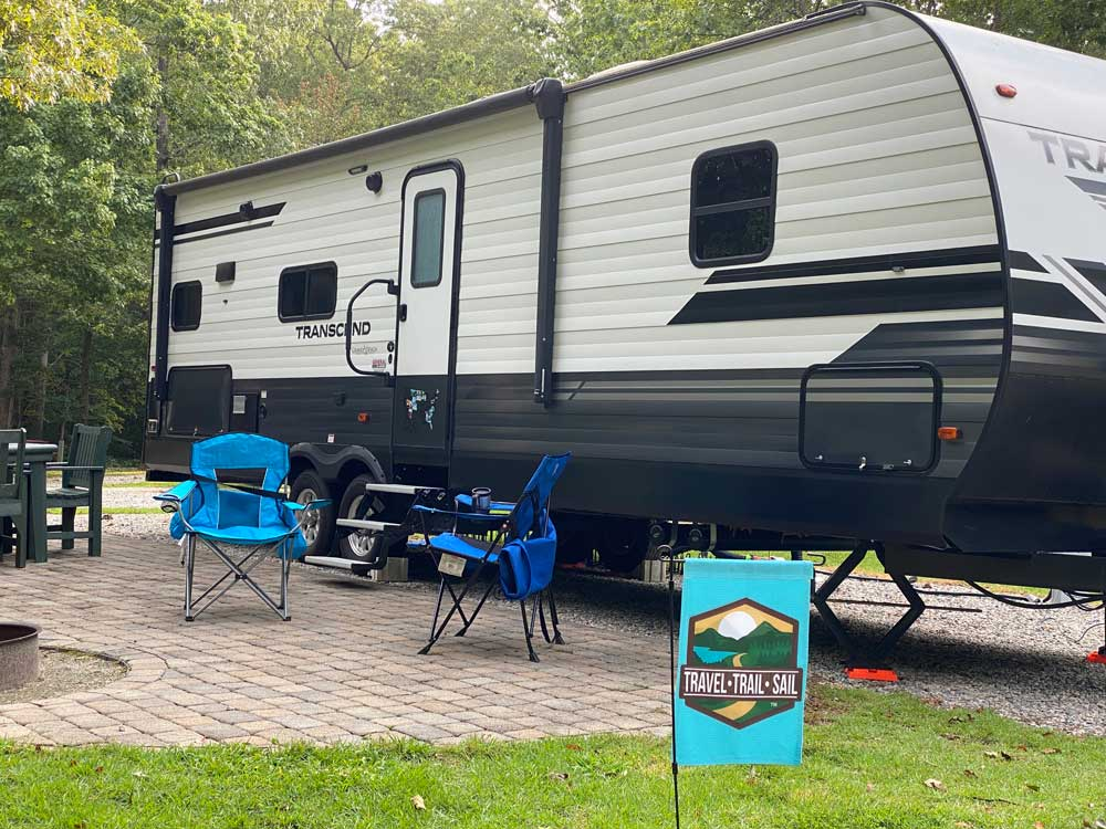 Travel Trailer on Campsite with Chairs and Garden Flag