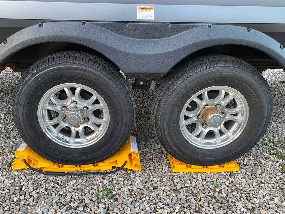 Camco chocks and blocks shown with travel trailer tires