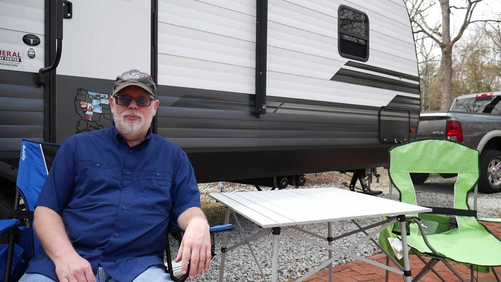 Coleman folding table set up by camper