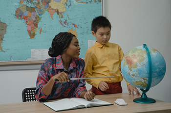 Teacher with student looking at Globe