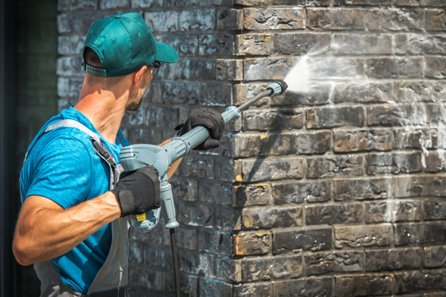 Workman cleaning a brick house as an exterior house cleaning service.
