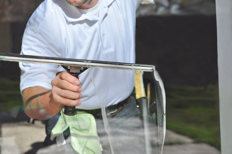 Man washing windows as part of his exterior house cleaning to-do list.