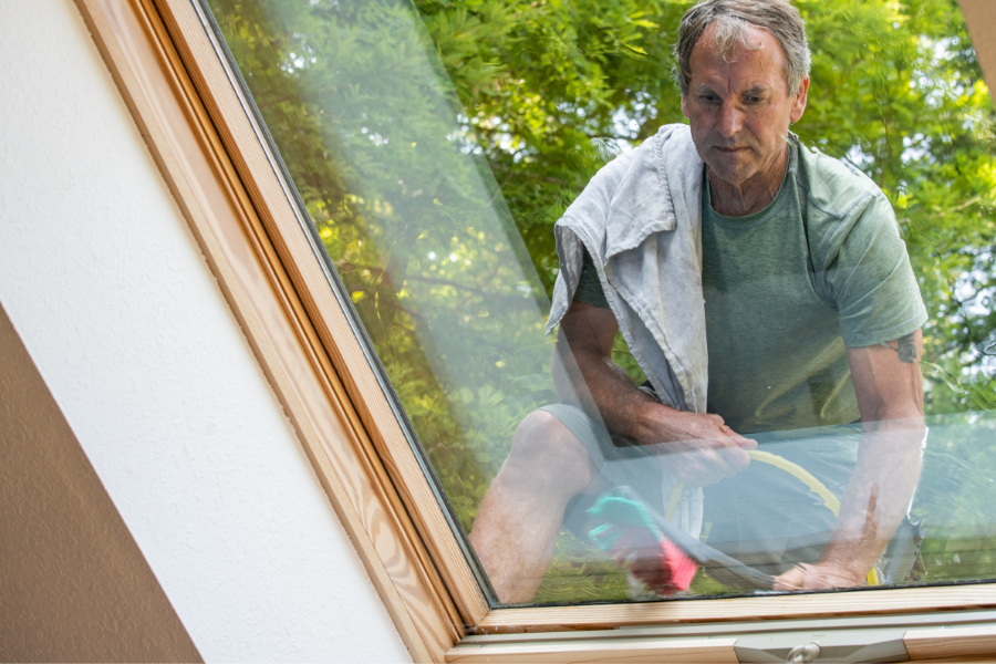 Middle-aged man using a brush to clean a skylight during roof cleaning.