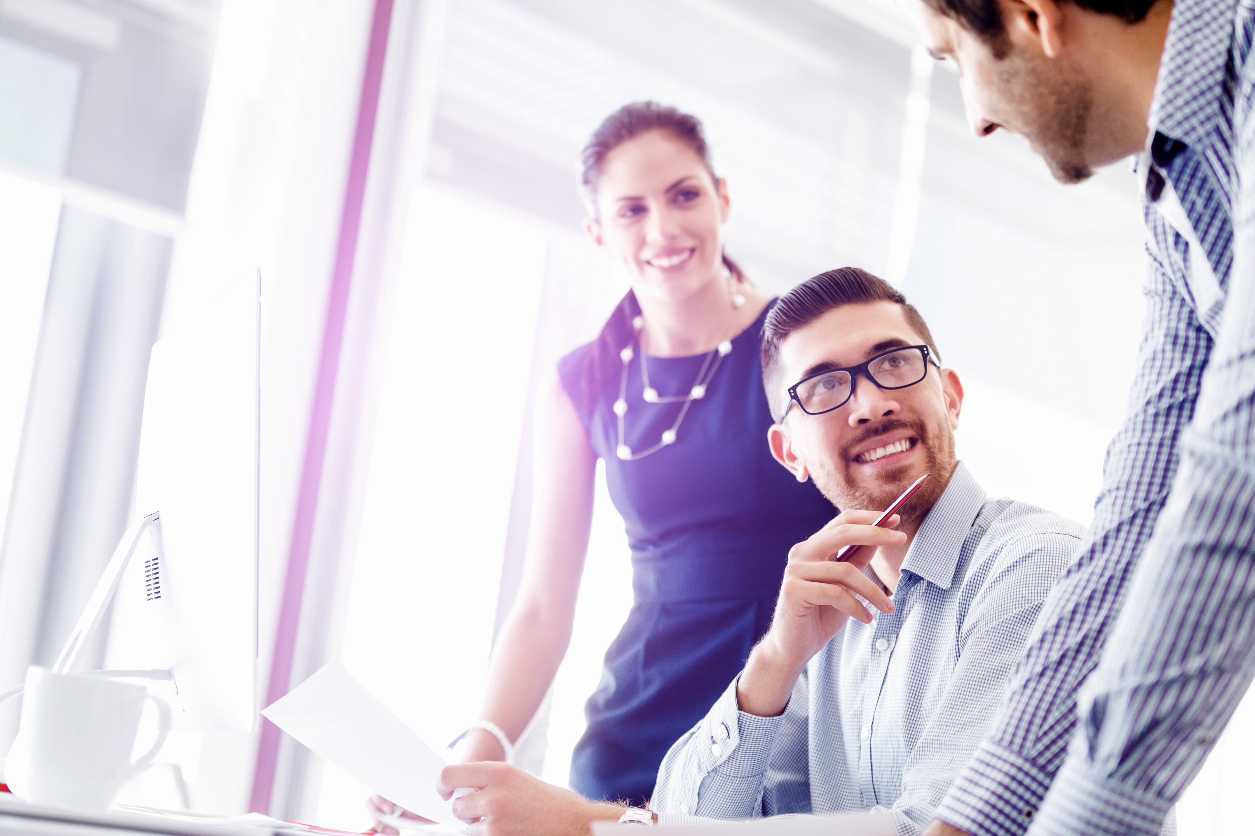 Young Businessman Sitting At Desk In Office And Talking To His Colleagues