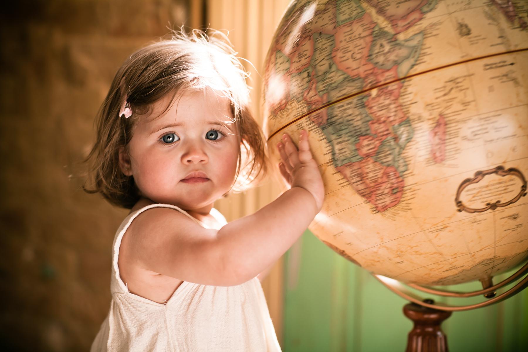 Girl with hand on globe