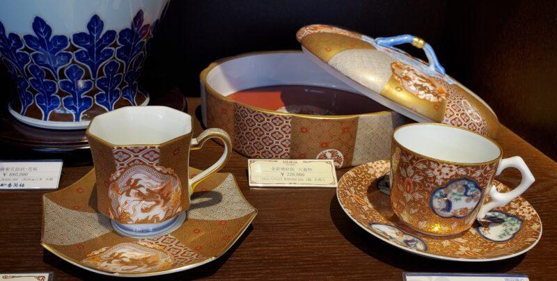 Чашка (слева) и блюдо с крышкой с рисунком дракона в золотом орнаменте и чашка (справа) с окошечками, демонстрирующими сосну, бамбук и сливу