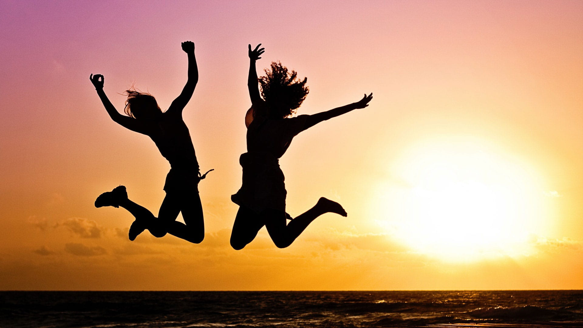 people jumping in air on beach at sunseet