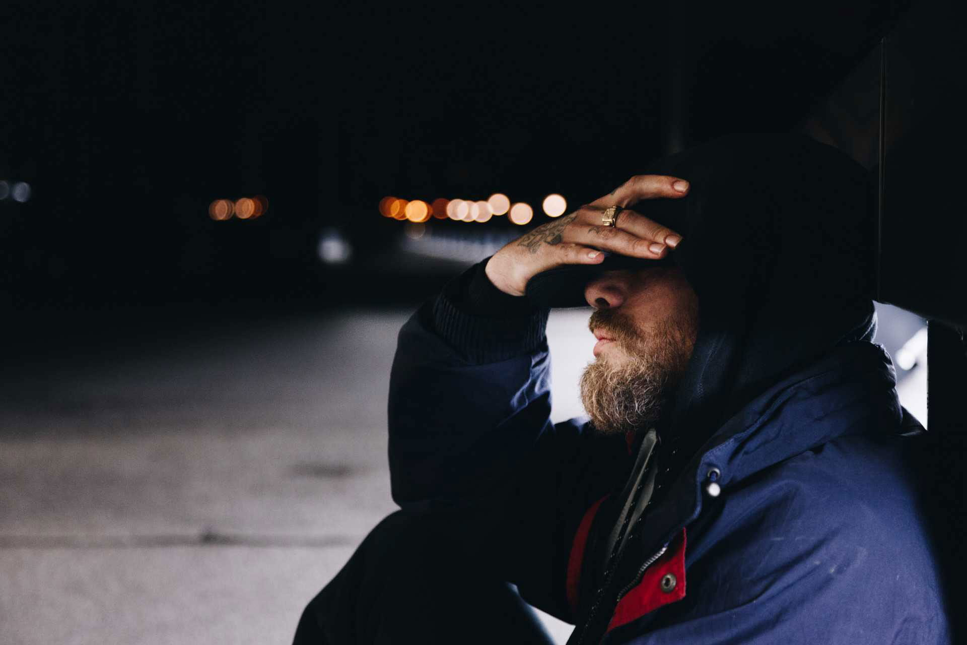 stressed man sitting on ground with hand on head