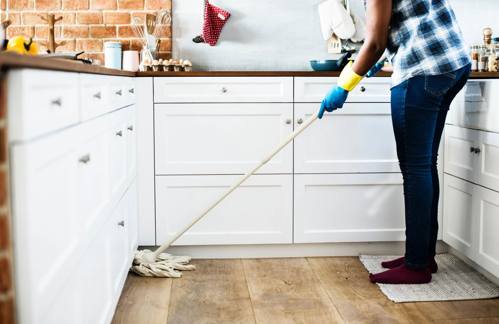 black woman mopping her kitchen floor