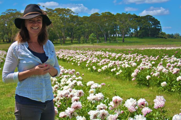 Nicky Barry in her paddock full of peonies
