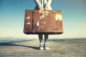 Girl with big, tattered suitcase