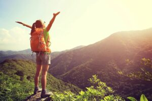 girl hiker at top of mountain with raised arms enjoy