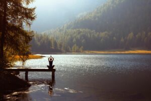 Women meditating on dock by an awe inspiring lake