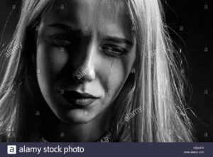 Black and white picture of girl with long blond hair looking sad