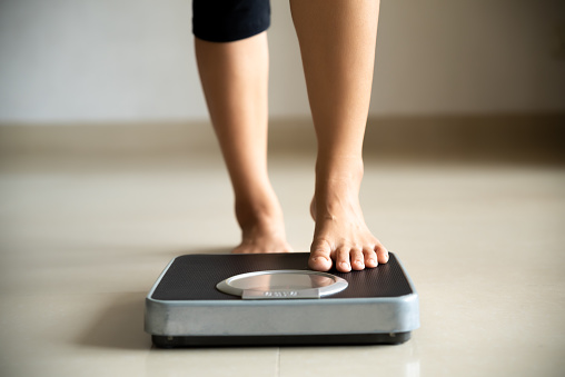Female leg stepping on weigh scales. Healthy lifestyle, good and sport concept.