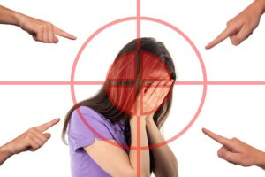 girl with hands over face and fingerings  on four sides pointing at her in blame