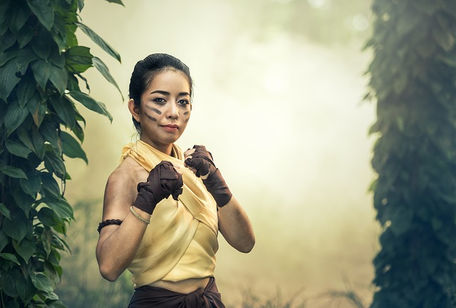 Asian woman in jungle, with boxing gloves ready to fight.