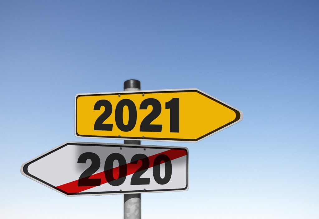 Two signs pointing in opposite directions. One is a 2000 crossed out in red and the other says 2021