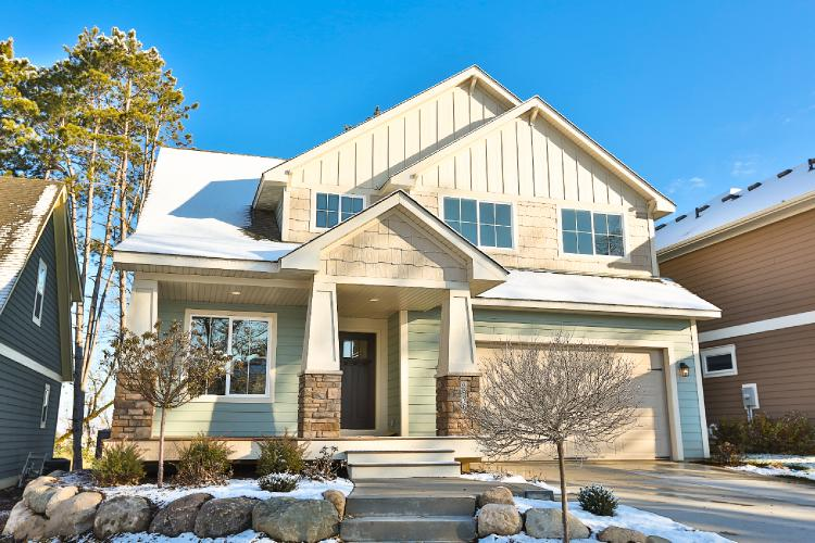 (This home is clad in HardiePlank® lap siding in minty green with HardiePanel® vertical siding and HardieShingle® siding in a creamy neutral. The varieties of siding styles on this quaint, snow-dusted home make it feel cozy and comfortable.)