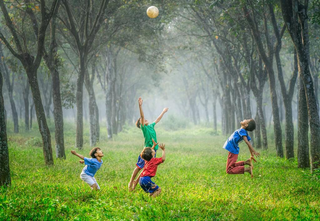 Boys playing soccer in field