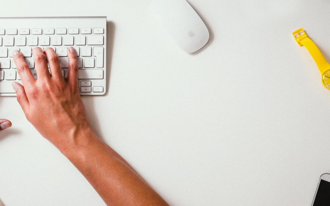 A pair of hands type on a keyboard type away with a wireless mouse, an analog watch and a phone sit nearby on the white desk