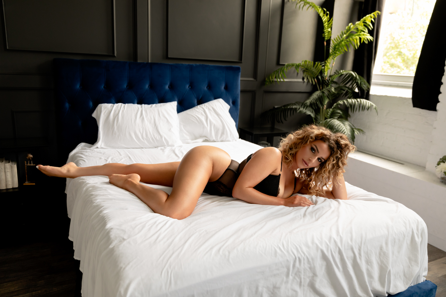 Black Female in a body suite laying on a bed in the best boudoir studio in Hampton Roads.
