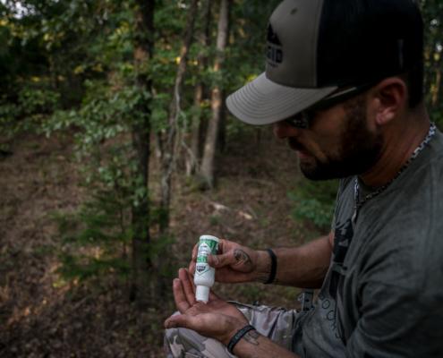 man applying an outdoor bug repellent