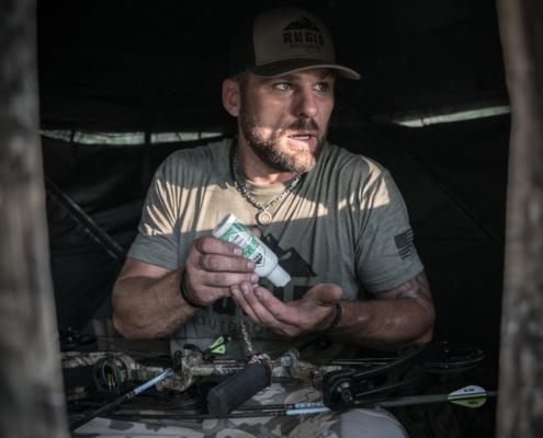 man using rugid bug repellent lotion