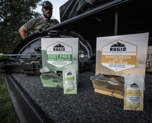 rugid single use repellent and sunscreen foil packs in a car boot