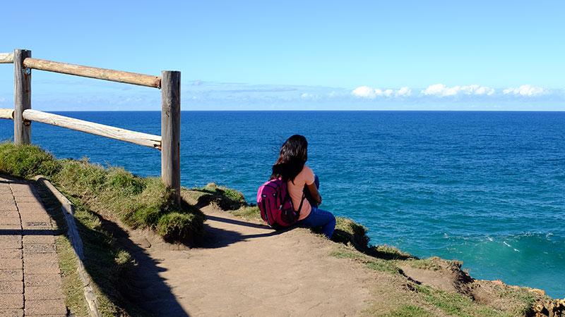 Woman sitting at Cape Byron. Credit: Chris Ashton