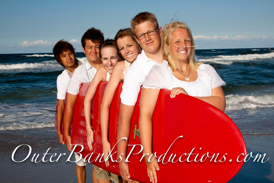 Bright red surfboard prop for family portraits.