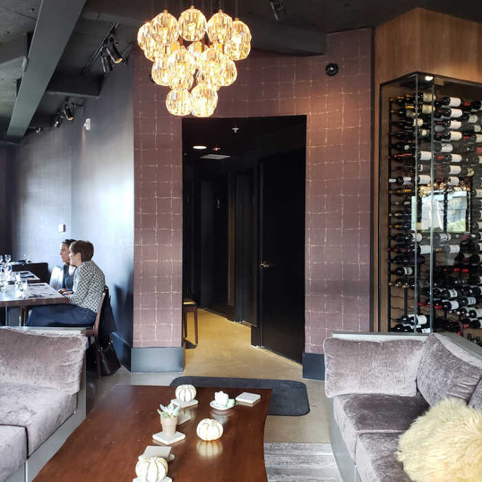 Restaurant Asa waiting area couches and wine collection