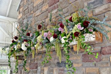 Romantic and elegant mantle design with greenery and pops of red, blue, purple and white