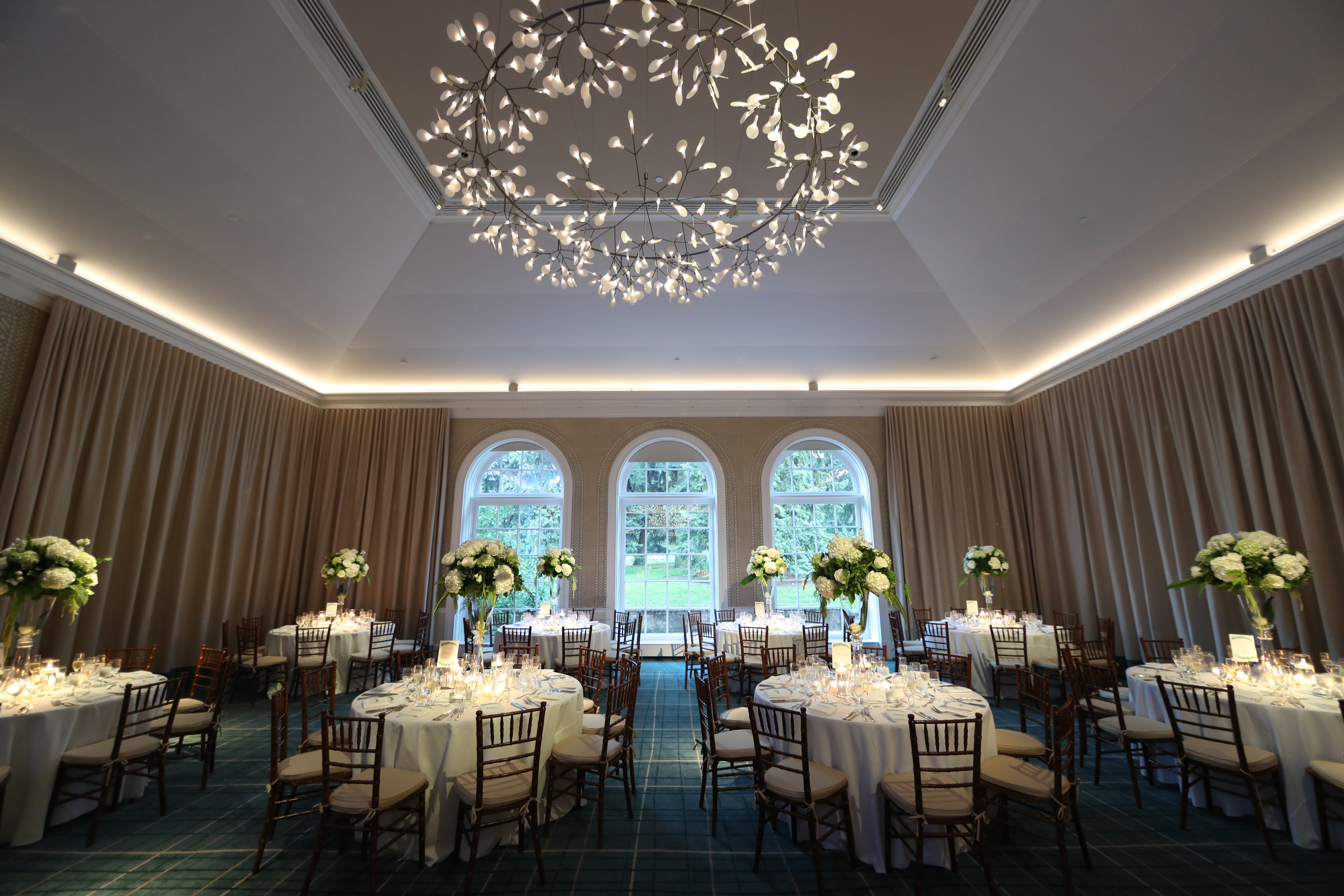 The chic ballroom at The New York Botanical Gardens that we designed using greenery and white roses for our bride and groom. See all the beautiful details on our blog!