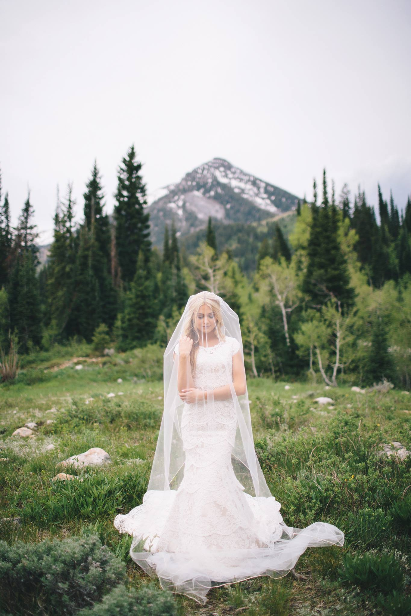 bride with veil covering her face standing in front of a mountain