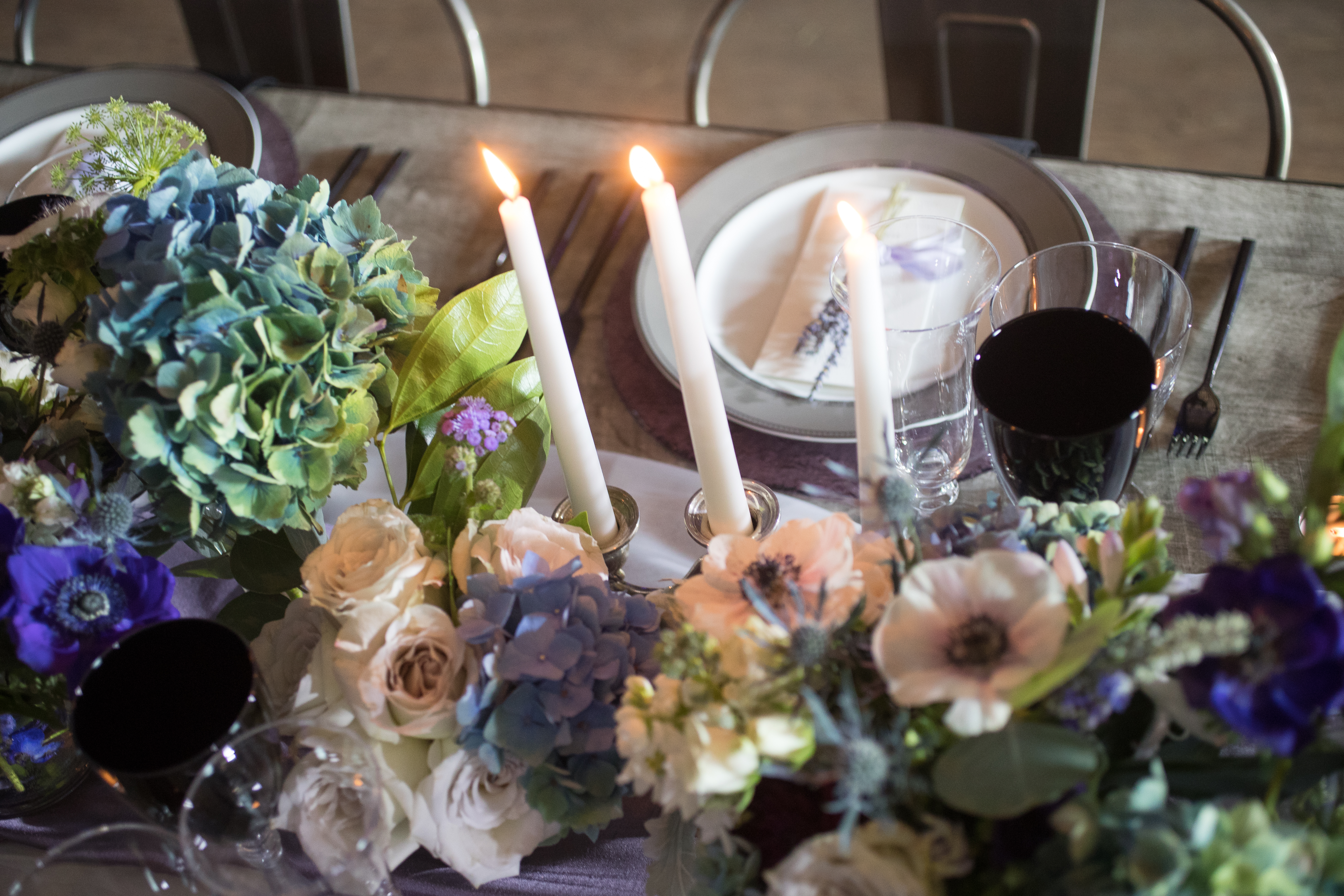 pictures of purple and blue flowers on gray tables with long white candles