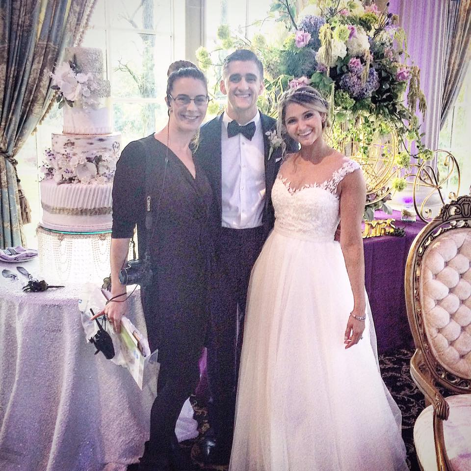 bride and groom with wedding planner in front of wedding cake