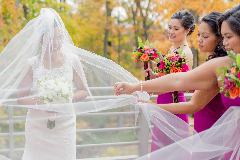 bridesmaids holding veil for bride