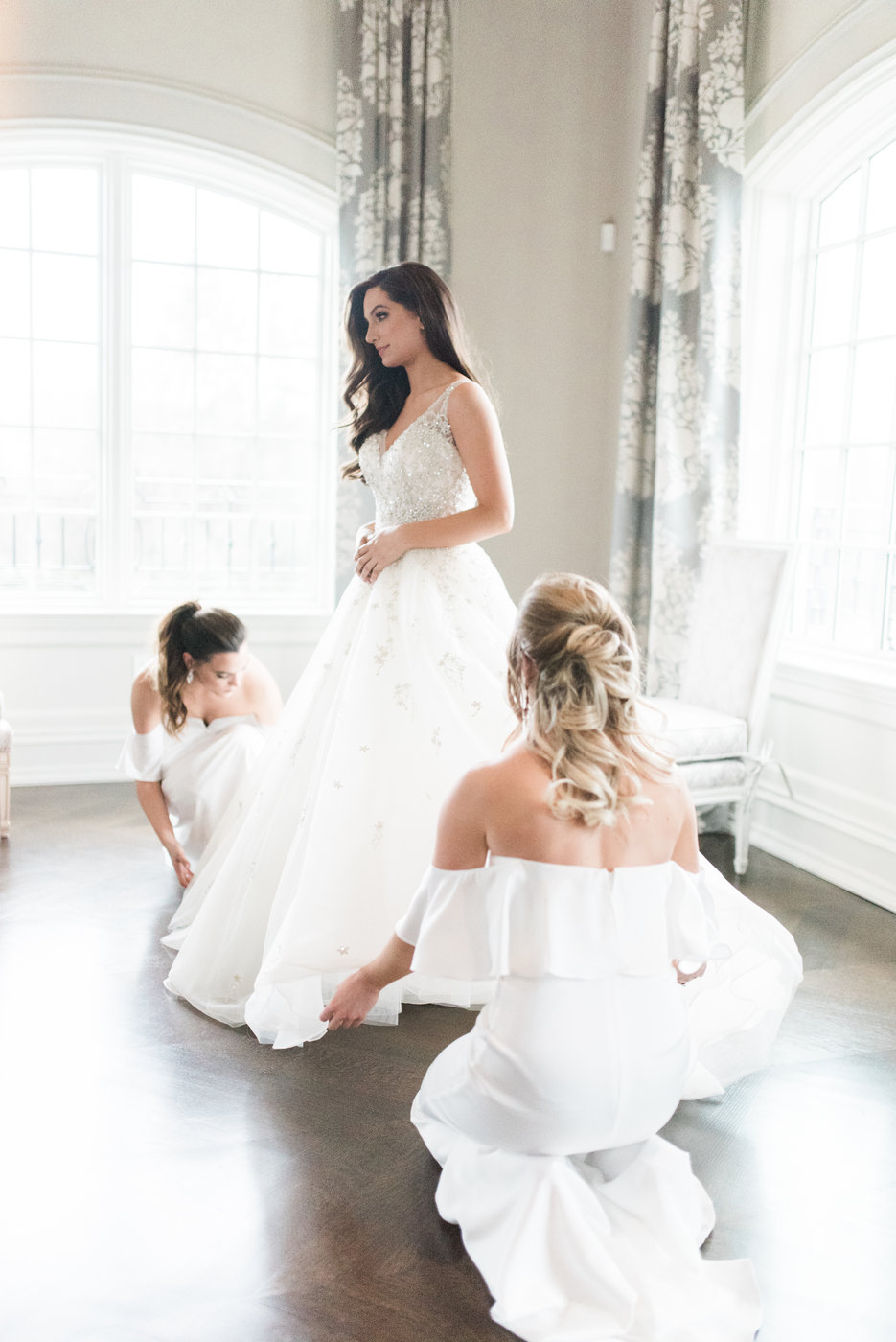 bride in gown being tended to by bridesmaids
