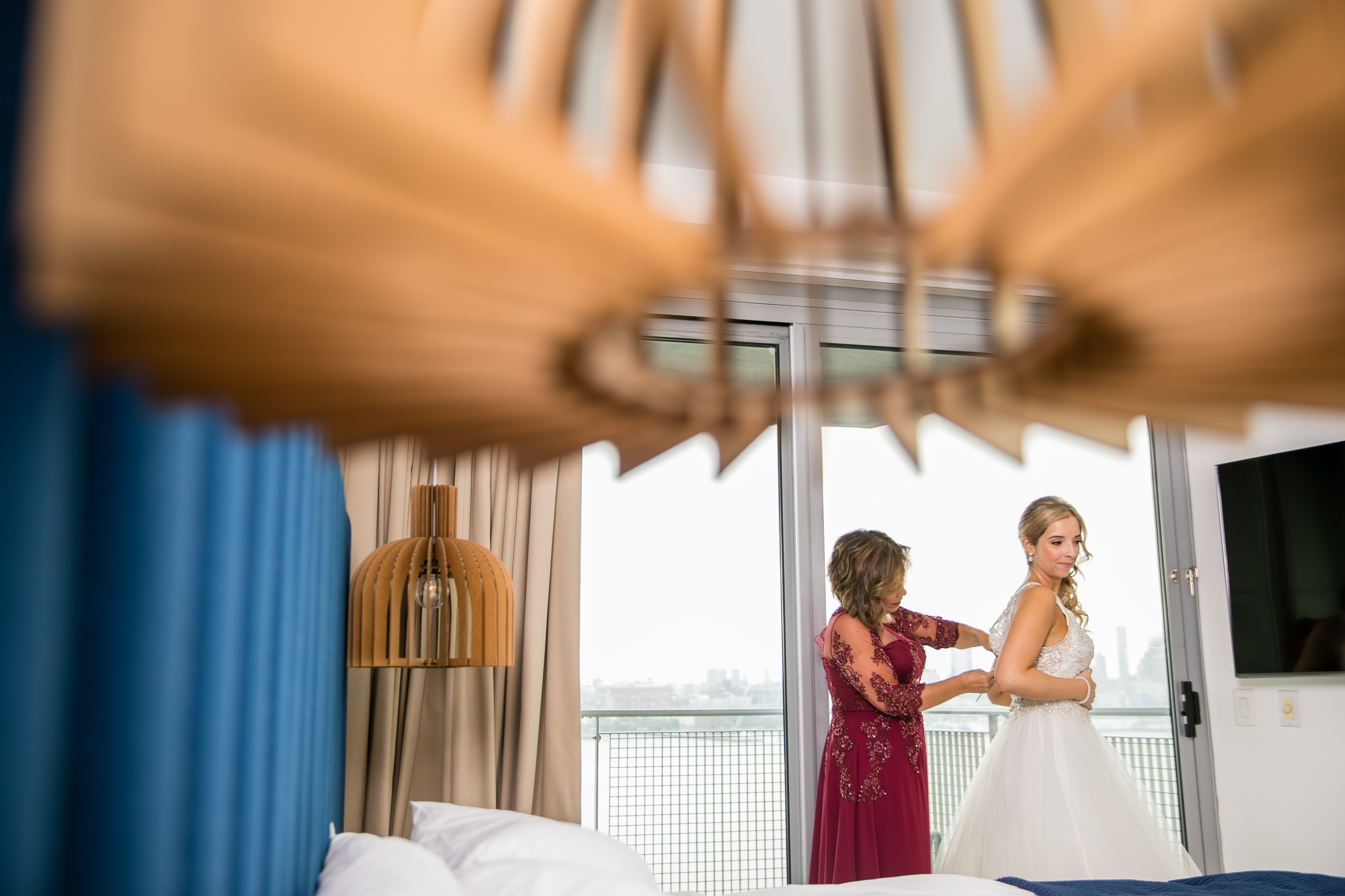 bride getting into gown with help from mother of the bride