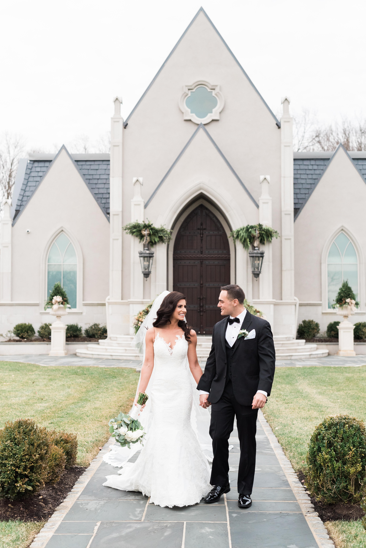bride and groom walking outside of wedding chapel