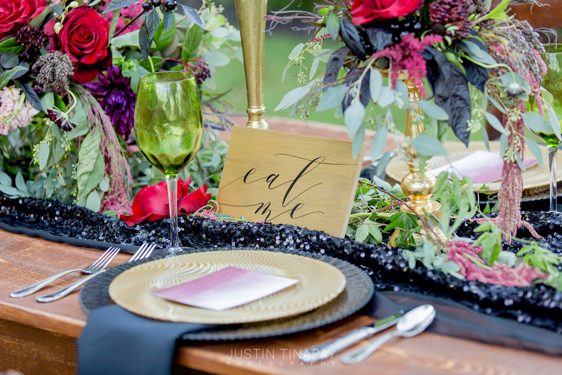 black and gold plates with black sequin runner on farmhouse table and red, purple, and green flowers