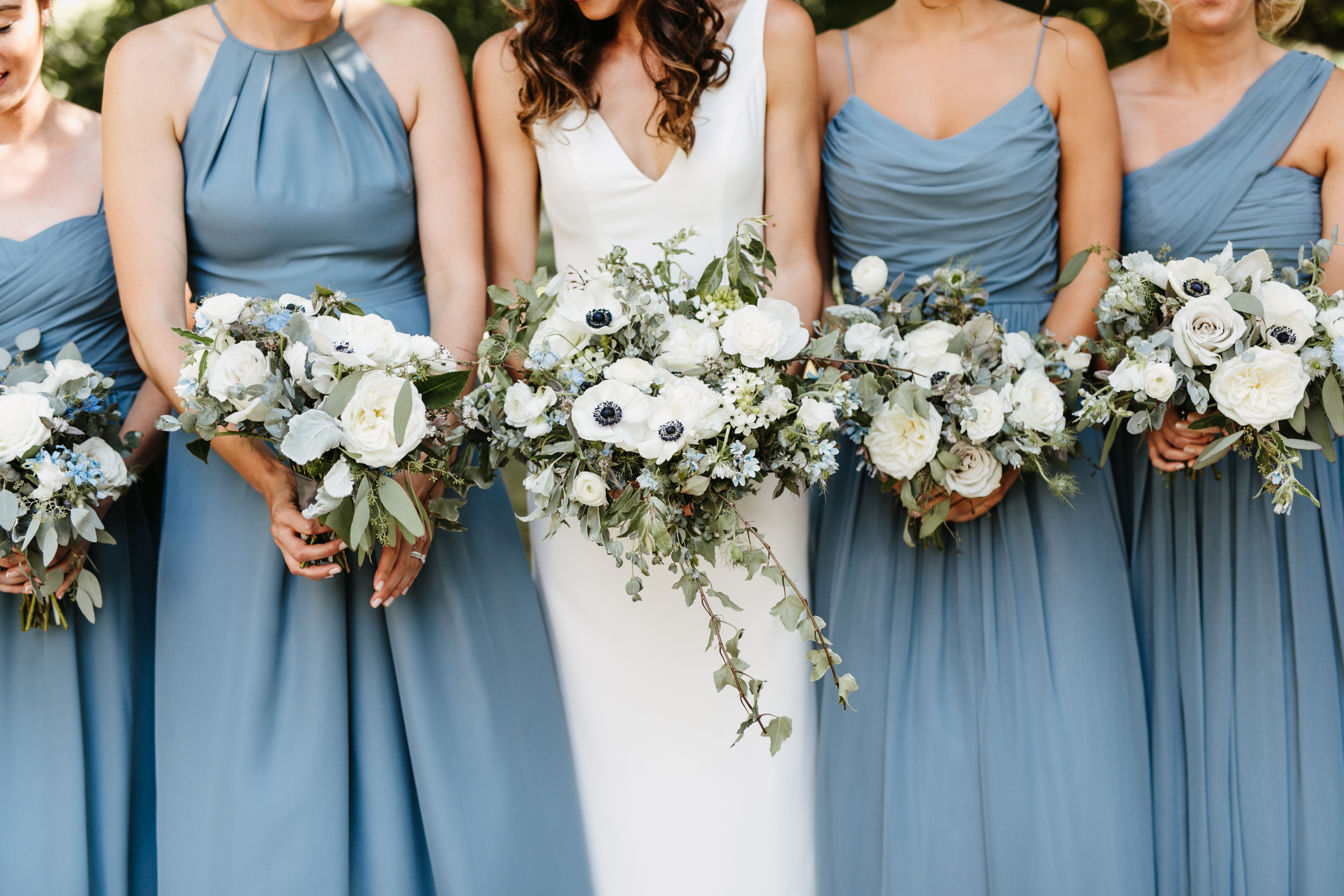 bridesmaids in blue holding bouquets